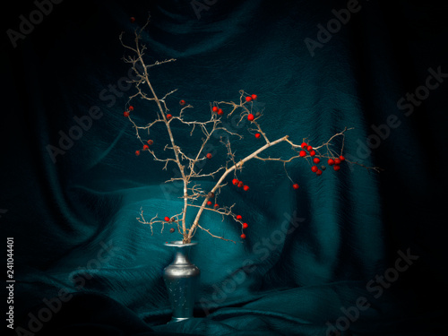 Fotografía  Winter red berries in a vase with turquoise fabric, light painting still life