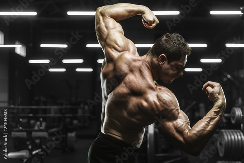 Fotografiet  Handsome strong athletic men pumping up muscles workout bodybuilding concept bac