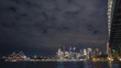 Central Sydney in night timelapse. Looking at the most iconic buildings of the city - Sydney Opera House and Sydney Harbour Bridge with the cityscape of central office towers between them.