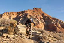 A Young Man Rides A Mountain Bike Over A Sandstone Ledge On The Jem Trail In The Desert Of Southern Utah.
