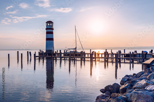 Fototapeten Leuchtturm Lighthouse at Lake Neusiedl, Podersdorf am See, Burgenland, Austria. Lighthouse at sunset in Austria. Wooden pier with lighthouse in Podersdorf on lake Neusiedl in Austria.