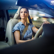 Pretty, young woman driving a car -Invitation to travel. Car rental, car ownership or vacation
