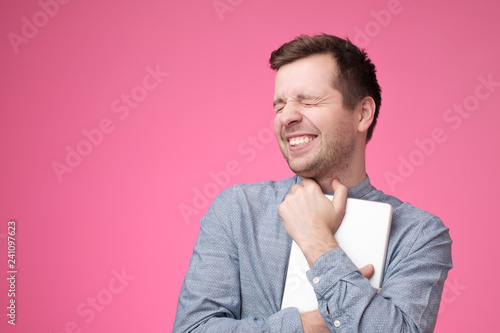 Happy young man holding tablet standing over pink wall - 241097623
