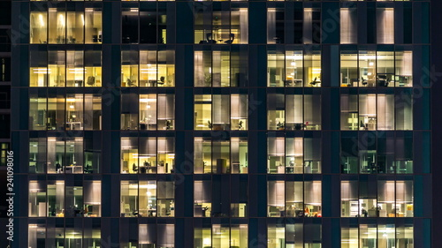 Obraz window of the multi-storey building of glass and steel lighting and people within timelapse - fototapety do salonu