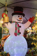 Vertical Image Of A Christmas Decoration Showing A Nice Inflatable Snowman In A Flower Shop