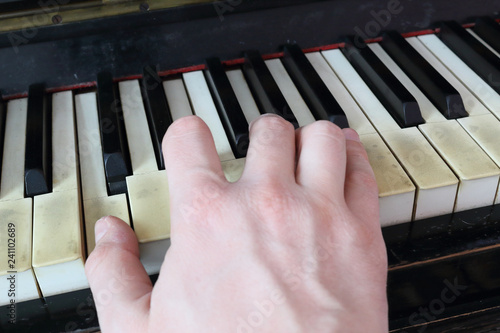 A right hand playing a C (DO) major chord on an old black piano with yellowed cr Slika na platnu