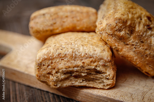 Foto op Plexiglas Brood Healthy homemade pastry with integral flour and seeds on kitchen cutting board. Wooden table and rustic vintage background.