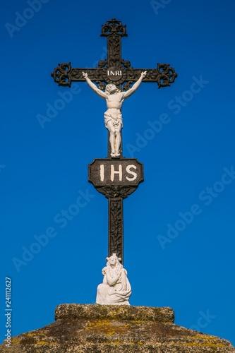 Fotografie, Obraz  Christian black iron crucifix with white sculpture of Jesus Christ crucifixion,