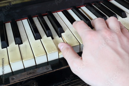 Fotografiet  A right hand playing a A (LA) major chord on an old black piano with yellowed cr