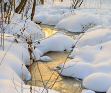 Frozen Stream In The Snow-covered Forest With Reflections Of The Morning, Evening Sun.