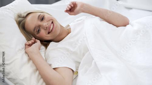 Healthy sleep on orthopedic mattress, happy teenage girl waking up with smile Wallpaper Mural