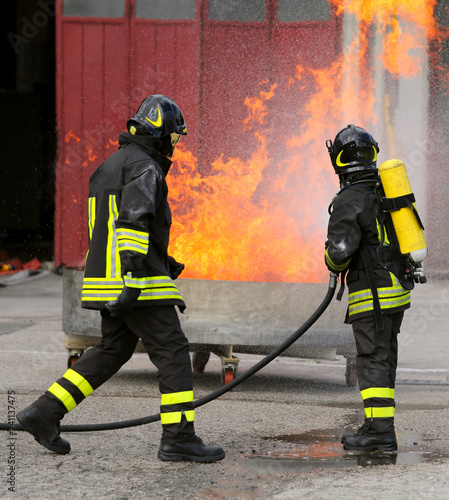 two intrepid firefighters during the exercise with a tank full o Canvas Print