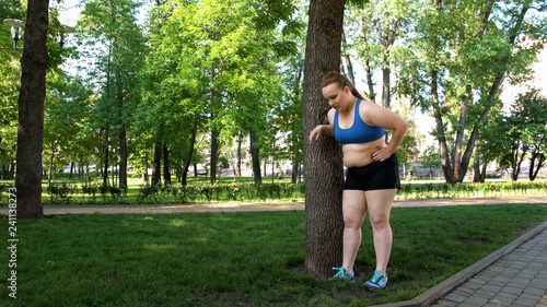 Fotografiet  Obese girl tired after jogging, leaning on tree, tiresome workouts outdoors