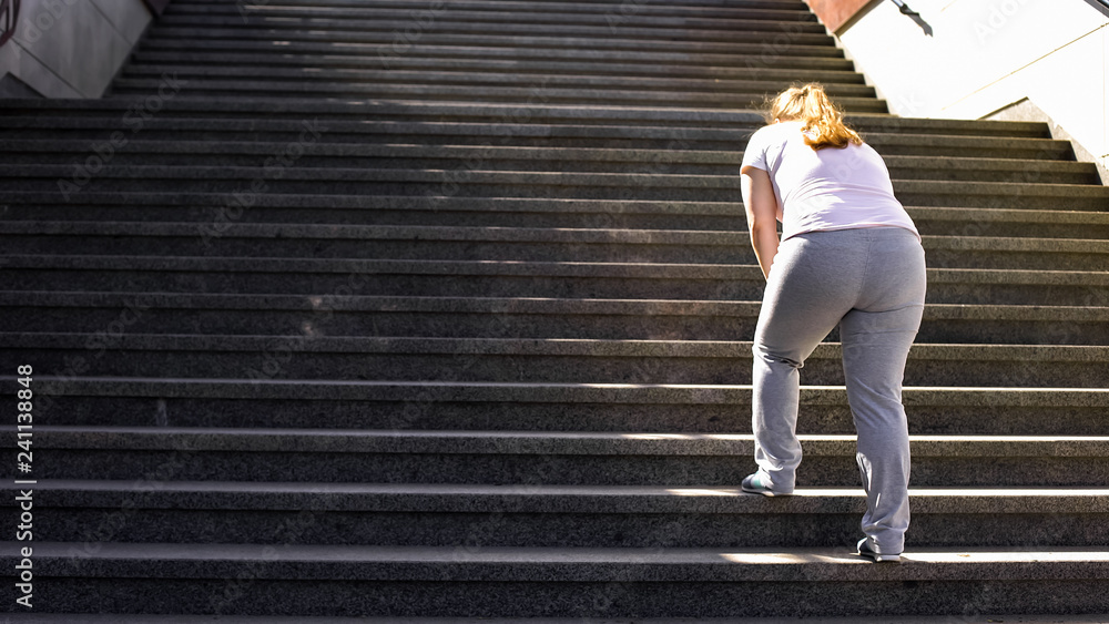 Fototapety, obrazy: Hard to climb stairs for obese girl, victory over fatigue for goal achieving