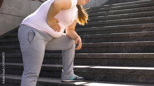 Leinwand Poster Fat girl feels ache in stomach, overweight causes health problems, back pain