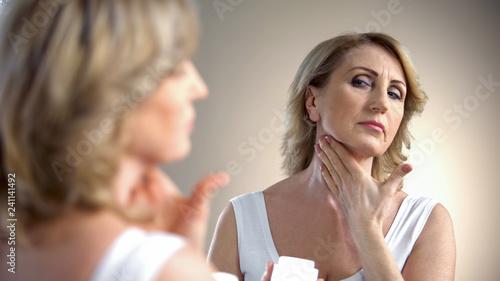Fotografía Elderly lady applying anti-age cream on neck, skin care in old age, wrinkles