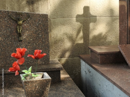 Fotografia, Obraz  Scene in a cemetery: a vase with red artificial flowers, a crucifix on a tombstone and the shadow of a cross on a stone wall
