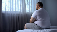 Sad Heavy Man Sitting On Bed At Home, Health Problem, Depression, Insecurities