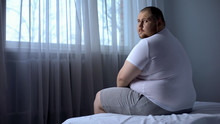 Sad Fat Man Sitting On Bed At ...