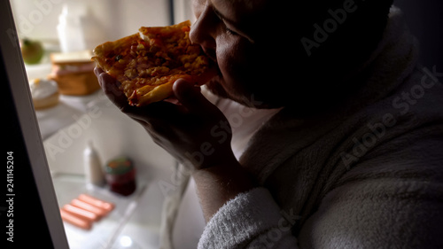 Unmotivated obese bachelor eating pizza near fridge at night, diet failure Canvas Print