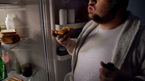 Fotomural Obese bachelor eating pizza near fridge, holding beer, unhealthy lifestyle