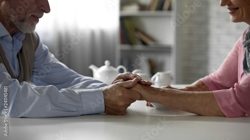 Fotografía Retiree husband holding tenderly wifes hand, having tea together, happiness