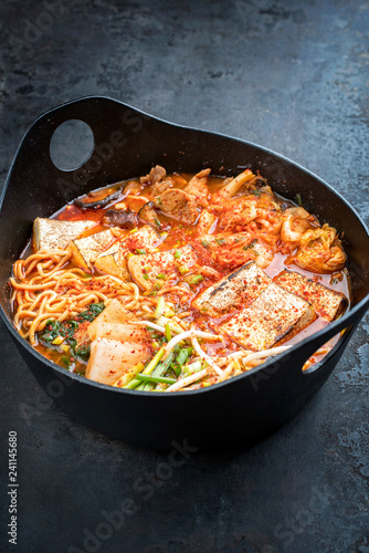 Traditional Korean kimchi jjigae with grilled pork belly and ramen as closeup in a modern design Japanese cast-iron roasting dish