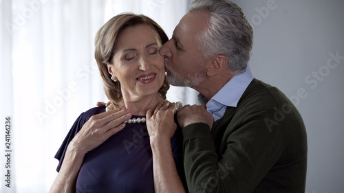 Valokuva  Aging male presenting pearl necklace to wife and kissing her celebration present