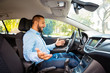 Side view of happy and surprised young businessman driving driverless car