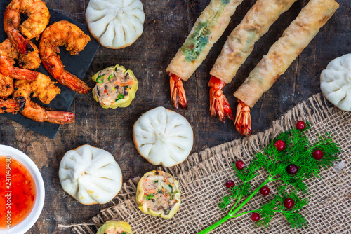 Giant king prawns and selection of mini Chinese dumplings with sweet chili dipping sauce. Party food idea. Top view