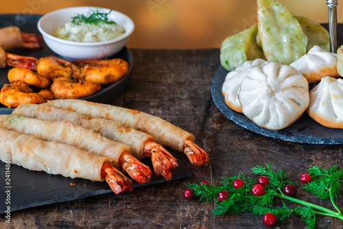 Giant king prawns and selection of mini Chinese dumplings with yogurt dipping sauces. Party food idea.