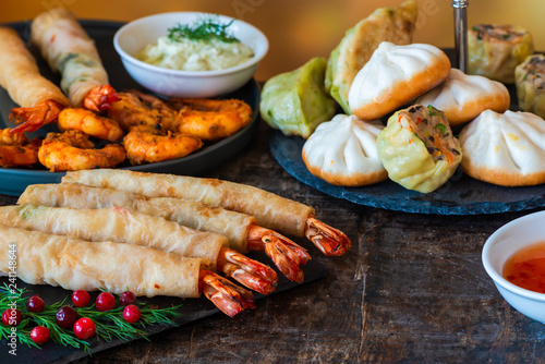 Giant king prawns and selection of mini Chinese dumplings with sweet chili and yogurt dipping sauces. Party food idea.