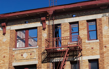 An Empty Old Roofless Building In Southern California Shows Blue Sky Through Open Windows. Fire Escape And Blond Brick.