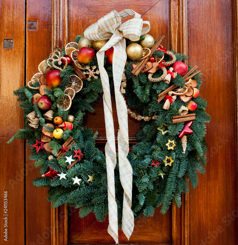 Fotografie, Obraz  Fabulous outdoor Christmas wreath ornamented with artificial fruit against woode