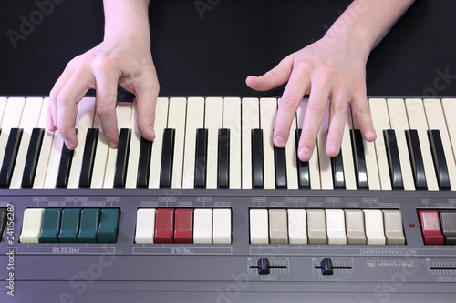 Fotomural  A right hand playing a G# sharp (SOL#) minor chord on an old black piano with ye