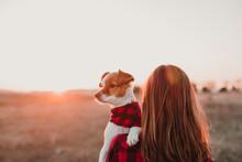 Woman And Dog At Sunset Wearing Same Plaid Shirt And Bandana. Outdoors