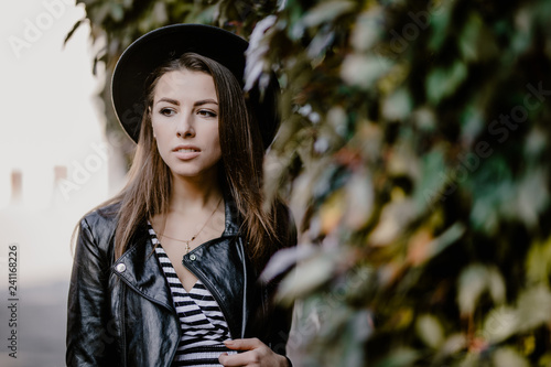 Portrait Of Young Woman In Fanky Hat Posing Near A Wall With