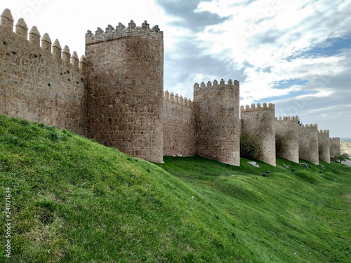 The wall of Avila, Spain. The stone wall with its turrets behind a green lawn.