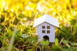Miniature white toy model house in meadow with grass. Eco Village, abstract environmental background. Real estate mortgage property insurance dream home ecology concept