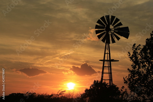 windmill at sunset with bright and colorful clouds.