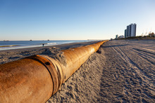 Myrtle Beach, South Carolina, United States - October 29, 2018: Old Rusty Pipes On The Sandy Beach During A Sunny Sunset.