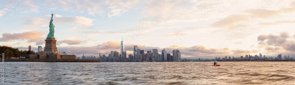 Fototapety, obrazy: Panoramic view of the Statue of Liberty and Downtown Manhattan in the background during a vibrant cloudy sunrise. Taken in Jersey City, New Jersey, United States.