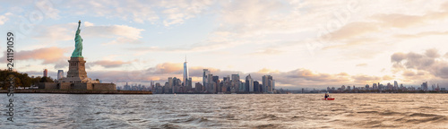 Cuadros en Lienzo Panoramic view of the Statue of Liberty and Downtown Manhattan in the background during a vibrant cloudy sunrise