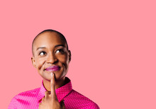 Portrait Of A Young Woman In Pink Shirt With Finger On Mouth Looking Up Thinking, Isolated On Pink Studio Background