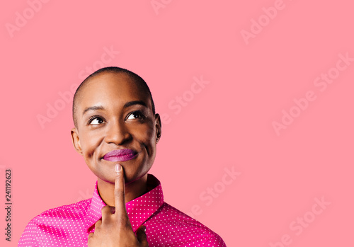 Fotografía Portrait of a young woman in pink shirt with finger on mouth looking up thinking