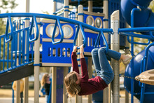 Girl Tween At Park Hanging From Monkey Bars Playground