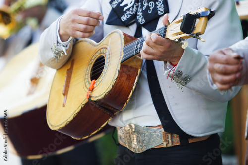 Mexican mariachi with white traditional costumes playing the vihuela at a party - 241196666