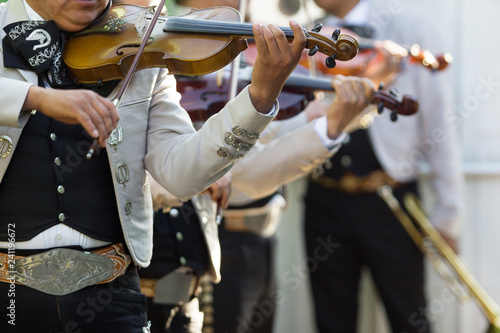 Mexican mariachi with white traditional costumes playing the violins at a party - 241196672