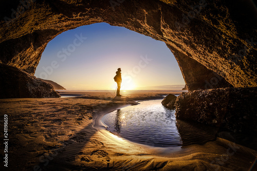 People explores a cave during sunrise at Wharariki Beach New Zealand Fototapete