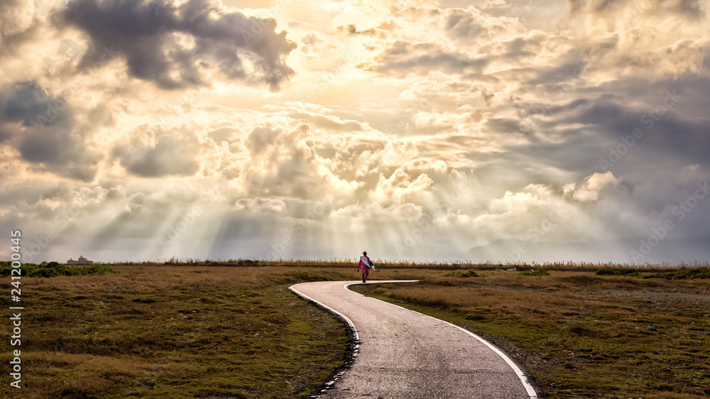Fototapeta Inspirational image of person walking along path with sun rays. Suitable for background use or adding text